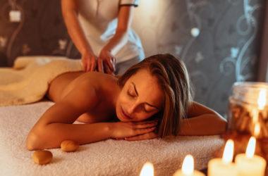 Frau auf Massageliege bekommt Rückenmassage bei Kerzenlicht
